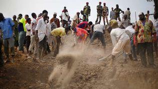 Sous le regard de soldats des troupes africaines, plusieurs personnes enterrent les corps de 16 musulmans, au nord de Bangui (Centrafrique). (JEROME DELAY / AP / SIPA)