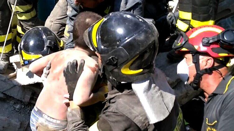 Les secouristes italiens extirpent Mattias, un petit garçon qui était coincé dans les décombres d'une maison, le 22 août 2017, après un tremblement de terre sur l'île italienne d'Ischia. (HANDOUT / VIGILI DEL FUOCO)