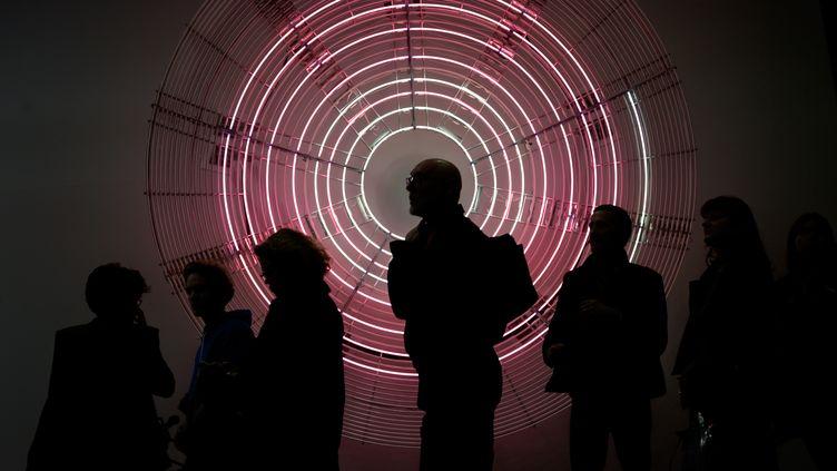 """Des visiteurs de la foire Art Basel devant une oeuvre de Carsten Holler, """"Decimal Clock (White and Pink)"""", Bâle (Suisse) le 12 juin 2019 (FABRICE COFFRINI / AFP)"""