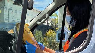 Une salariée d'Amazon lors d'une livraison, le 8 avril 2020, àLos Angeles, aux Etats-Unis. (CHRIS DELMAS / AFP)
