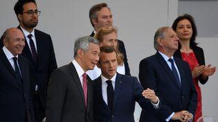 Emmanuel Macron en conversation avec le Premier ministre de Singapour, le 14 juillet 2018. (ERIC FEFERBERG / AFP)