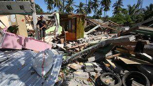 Un homme marche dans les décombres de sa maison, après le séisme à Lombok (Indonésie), le 11 août 2018. (KOJI ITO / YOMIURI)