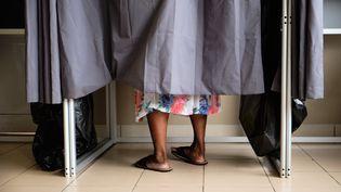 Une électrice de Nouméa dans l'isoloir d'un bureau de vote, le 15 mars 2020, à l'occasion du premier tour des municipales. (THEO ROUBY / AFP)