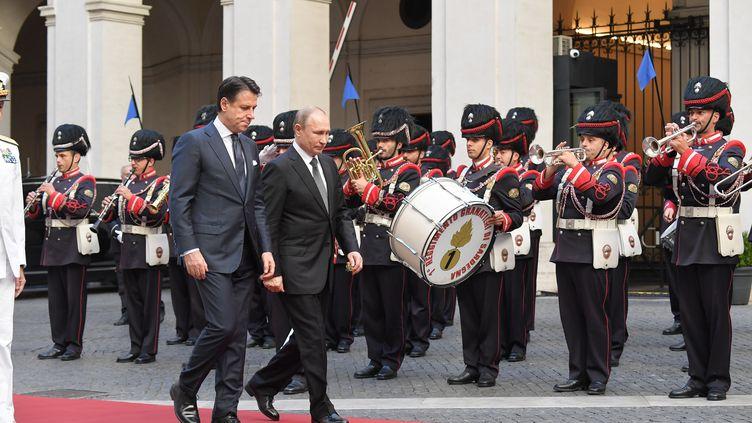 Le Premier ministre italien Giuseppe Conte (à gauche) et le président russe Vladimir Poutine (à droite) passent en revue un régiment militaire à leur arrivée au Palazzo Chigi, à Rome, le 4 juillet 2019. (TIZIANA FABI / AFP)