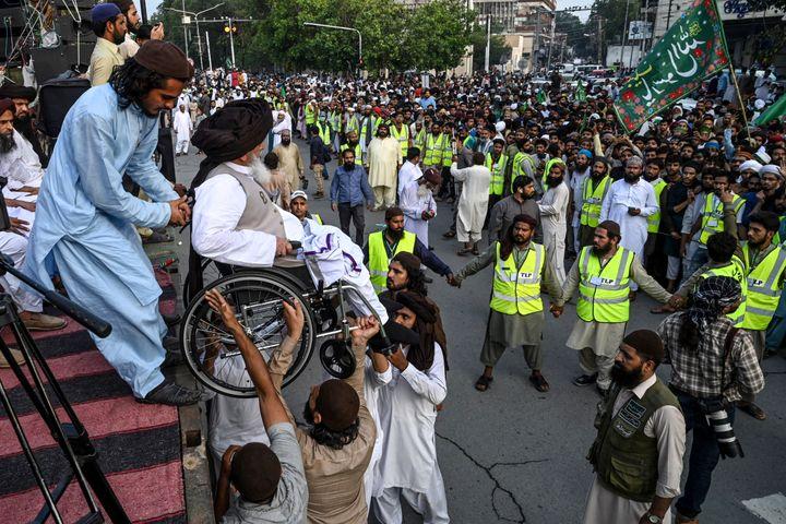 """Khadim Hussain Rizvi, en fauteuil roulant, est descendu d'une scène lors d'un rassemblement contre la republication de caricatures de Mahomet par """"Charlie Hebdo"""", le 4 septembre 2020, à Lahore (Pakistan). (ARIF ALI / AFP)"""