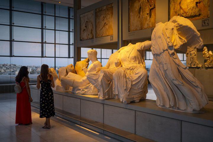 Deux visiteuses au musée de l'Acropole d'Athènes Acropolis ouvert la nuit du 22 août 2021 (ANGELOS TZORTZINIS / AFP)