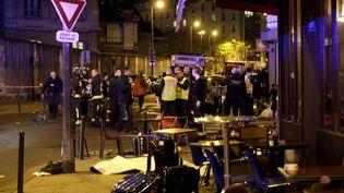 Des forces de sécurités et des blessés devant le lieu d'une des fusillades survenue vendredi 13 novembre 2015, à Paris. (PHILIPPE WOJAZER / REUTERS)
