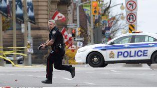 Un policier canadien accourt près du Parlement à Ottawa (Canada), où a lieu une fusillade, le 22 octobre 2014. (SEAN KILPATRICK/AP/SIPA / AP)