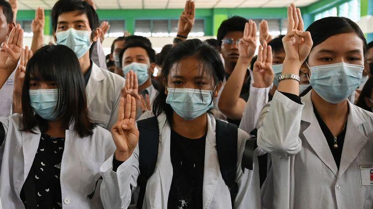 Des étudiants en médecine font le salut à trois doigts, emblème de la mobilisation contre le coup d'Etat militaire, lors des obsèques de Khant Nyar Hein, abattu pendant une manifestation, le 16 mars 2021 à Rangoun (Birmanie). (AFP)