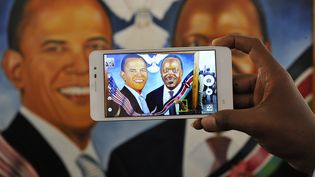 Des centaines de tableaux à l'effigie de Barack Obama sont affichés dans Nairobi. Ici, un homme prend en photo le portrait d'Obama avec son homologue kényan le président Uhuru Kenyatta. (SIMON MAINA / AFP)
