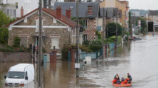 Des sauveteurs de la Sécurité civile évacuent des riverains àJuvisy-sur-Orge (Essonne), le 3 juin 2016. (CHRISTIAN HARTMANN / REUTERS)