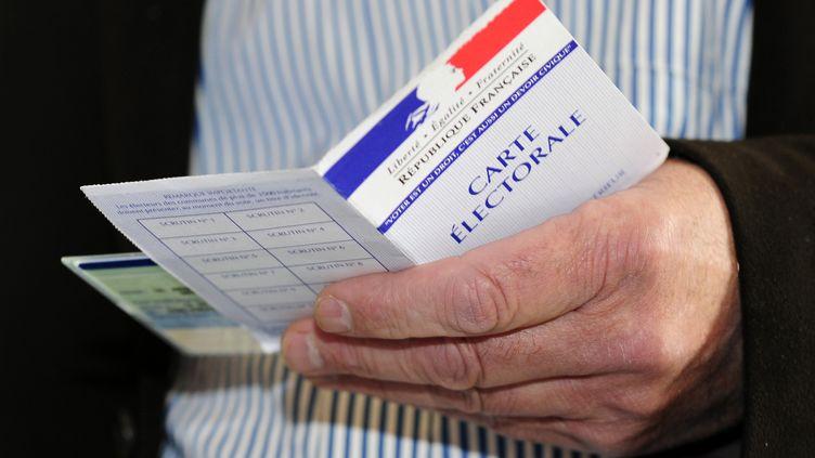 Un homme tenant une carte d'électeur en mai 2012 dans les Yvelines. (FRÉDÉRIC SOREAU / PHOTONONSTOP / AFP)