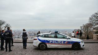 Une voiture de police et des policiers à Paris le 17 mars 2020. (MATHIEU MENARD / HANS LUCAS / AFP)
