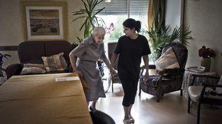 Une personne âgée et son aide à domicile. Photo d'illustration. (JEFF PACHOUD / AFP)