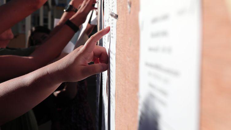 Des étudiants devant les résultats du bac. (RICHARD BOUHET / AFP)