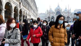 Des touristes portant des masques sur la place Saint-Marc, à Venise en Italie, le 24 février 2020. (ANDREA PATTARO / AFP)