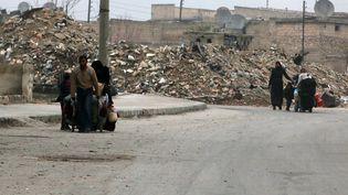 Des personnes transportent leurs affaires personnelles au milieu des décombres à Alep (Syrie), le 5 décembre 2016. (ABDALRHMAN ISMAIL / REUTERS)