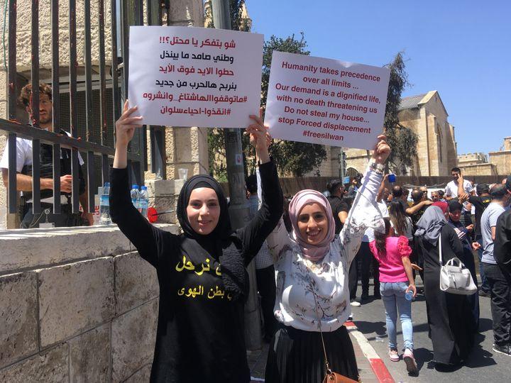 Deux manifestantes brandissent des pancartesdevant l'entrée du tribunal de Jérusalem en soutien auxfamilles de Silwan, menacées d'expulsion, le 26 mai 2021. (FARIDA NOUAR / RADIO FRANCE)