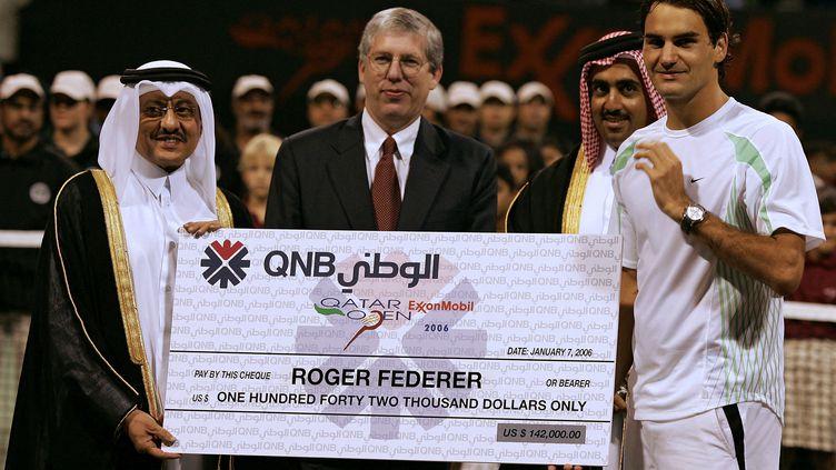 Un chèque est remis à Roger Federer après sa victoire dans le tournoi de Doha, le 7 janvier 2006. (KARIM JAAFAR / AFP)