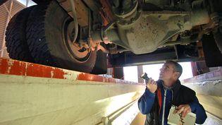 Un controleur technique automobile vérifie l'état d'un essieu. (ERIC FEFERBERG / AFP)