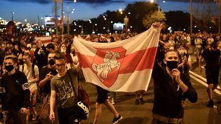 Des opposants à Alexandre Loukachenko défilent dans les rues de Minsk (Biélorussie) après la clôturedes bureaux de vote lors de l'élection présidentielle, dimanche 9 août 2020. (SERGEI GAPON / AFP)