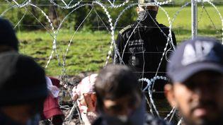 Un garde-frontière polonais face à des migrants du côté de la Biélorussie, le 29 septembre 2021. (VIKTOR TOLOCHKO / SPUTNIK / AFP)
