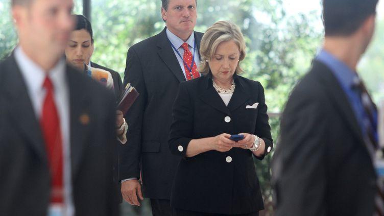Hillary Clinton, alorssecrétaire d'Etat, consulte son téléphone à Hanoï, au Vietnam, le 23 juillet 2010. (NA SON NGUYEN / AFP)