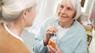 Une femme âgée boit une boisson énergisante pour prévenir la dénutrition. (BURGER / PHANIE / AFP)