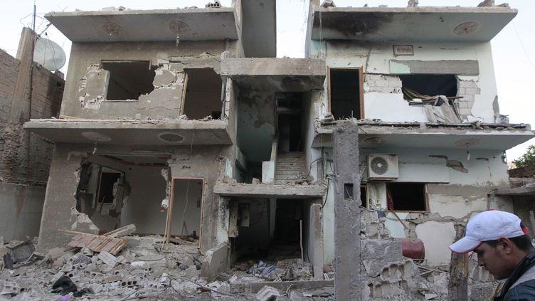 Un immeuble de Raqqa (Syrie) touché par un bombardement aérien de l'armée syrienne, le 28 novembre 2014. (STRINGER / ANADOLU AGENCY / AFP)