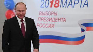 Vladimir Poutine sourit devant les caméras à l'occasion de son vote pour la présidentielle, le 18 mars 2018, à Moscou (Russie). (YURI KADOBNOV / REUTERS)
