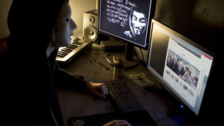 Un pirate se revendiquant du collectif Anonymous devant son ordinateur, le 20 janvier2012, à Lyon. (JEAN-PHILIPPE KSIAZEK / AFP)