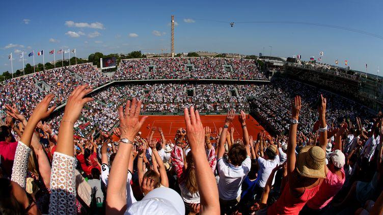 Le public de Roland-Garros fait la ola pendant la finale dames Sharapova-Halep, le 7 juin 2014 à Paris. (CLIVE BRUNSKILL / GETTY IMAGES)