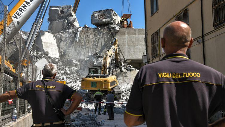 Des pompiers participent aux opérations de secours sur les lieux de l'effondrement du viaduc Morandi de Gênes (Italie), jeudi 16 août 2018. (PIERO CRUCIATTI / AFP)