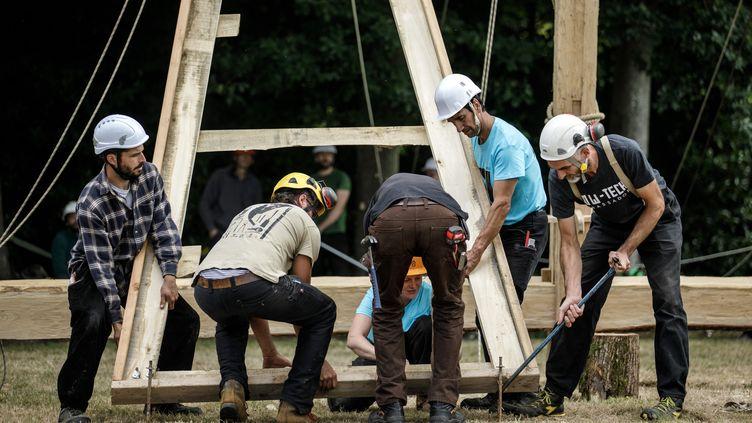 Des membres de Charpentiers sans frontières au travail sur la réplique d'une des structures de la nef de Notre-Dame, réalisée avec les techniques d'origine, à Ermenouville (Normandie, France), le 7 juillet 2020. (SAMEER AL-DOUMY / AFP)