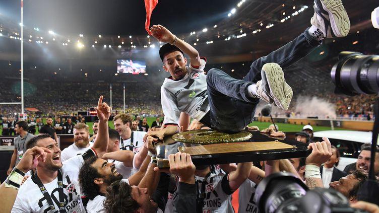 Après leur victoire en finale du Top 14, les rugbymen du Stade toulousain transportent le chanteur Oli sur le bouclier de Brennus. (ALAIN JOCARD / AFP)