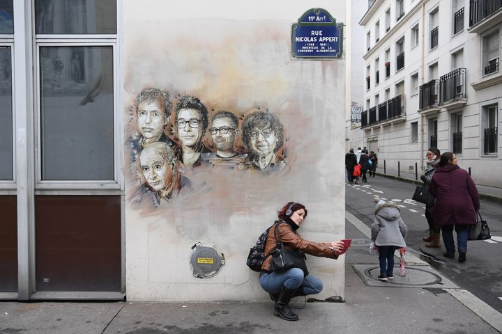"""Une passante prend un selfie devant les portraits des victimes de l'attentat de """"Charlie Hebdo"""", peints sur la facade d'un bâtiment de la rue Nicolas-Appert, le 7 janvier 2018. ((CHRISTOPHE ARCHAMBAULT / AFP))"""