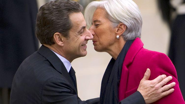 Nicolas Sarkozy et Christine Lagarde se font la bise devant l'Elysée, le 11 janvier 2012, à Paris. (LIONEL BONAVENTURE / AFP)