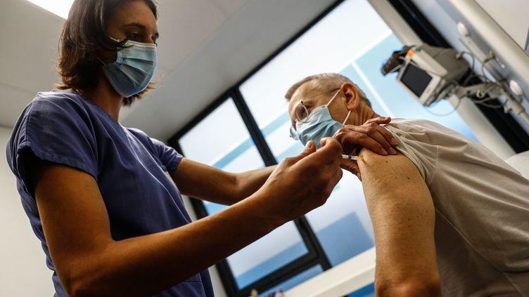 Une infirmière administre une dose de vaccin contre le Covid-19 à un soignant de plus de 50 ans à l'Hôtel-Dieu à Paris, le 2 janvier 2020. (SAMEER AL-DOUMY / AFP)