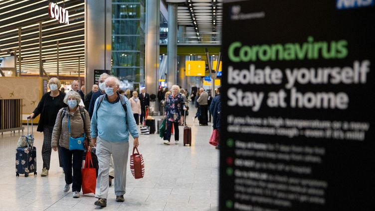 Des passagers à l'aéroport d'Heathrow à Londres, le 19 mars 2020. (TOLGA AKMEN / AFP)