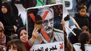 Une manifestante frappe avec une chaussure le portrait du maréchal Haftar, à Tripoli, le 27 décembre 2019. (MAHMUD TURKIA / AFP)