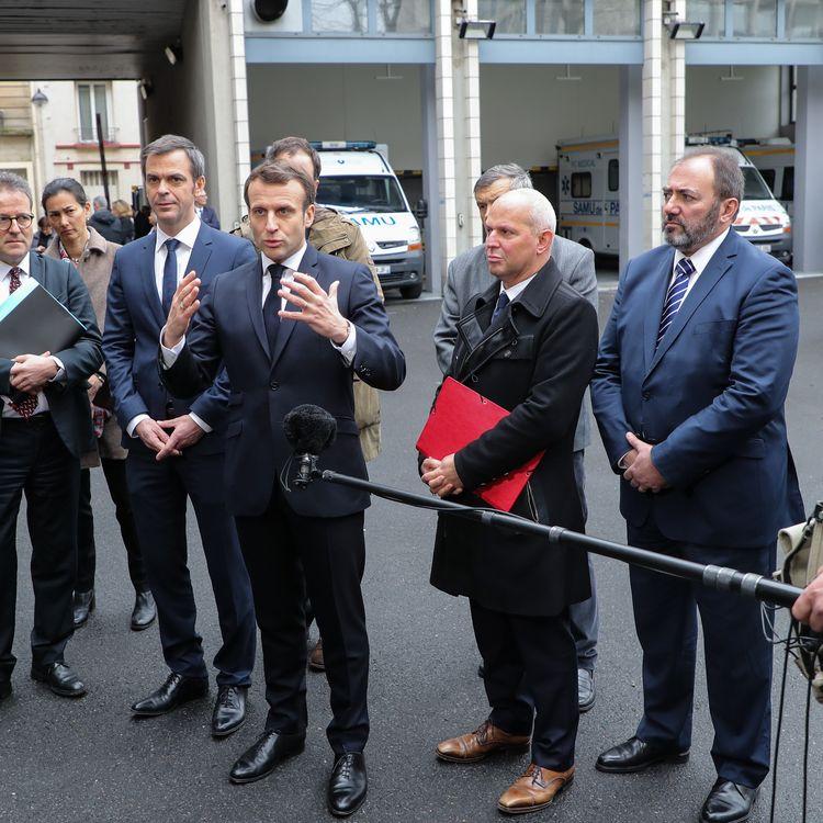 Le président de la République, Emmanuel Macron, accompagné du ministre de la Santé, du directeur général de la Santé et du président de l'AP-HP, lors d'une visite à l'hôpital Necker à Paris, le 10 mard 2020. (LUDOVIC MARIN / AFP)