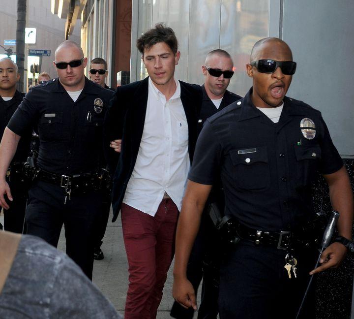 Le journaliste ukrainien Vitalii Sediuk emmené par la police après avoir frappé Brad Pitt à Hollywood (Etats-Unis), le 28 mai 2014. (GREGG DEGUIRE / WIREIMAGE / GETTY IMAGES)