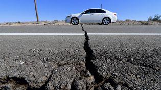 Une voiture circule sur l'autoroute 178, fissurée par le séisme du 4 juillet 2019, en Californie. (FREDERIC J. BROWN / AFP)