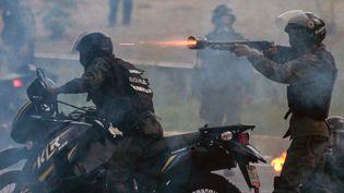 Des membres de la garde nationale bolivarienne tirent lors d'une manifestation de l'opposition contre le président du Venezuela, Nicolas Maduro, à Caracas, le 6 juillet 2017. (FEDERICO PARRA / AFP)