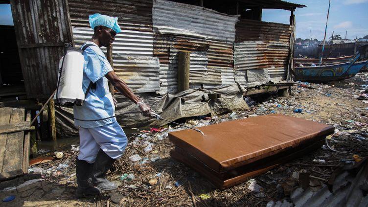 (Une infirmière libérienne désinfecte un matelas pillé © MaxPPP)