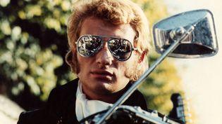 """Johnny Hallyday et ses rouflaquettes apparaissent dans le film """"A tout casser"""", en 1968. (COMPAGNIE COMMERCIALE FRANCAISE / AFP)"""