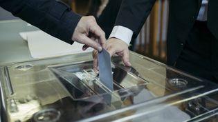 Un électeur glisse son bulletin dans l'urne, le 7 mai 2017, lors du second tour de l'élection présidentielle, dans le 20e arrondissement de Paris. (DENIS MEYER / HANS LUCAS / AFP)