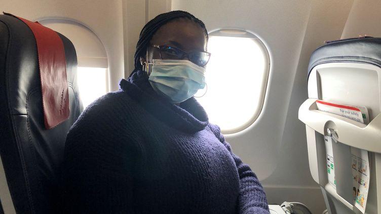 Régine Yao, dans un avion de la compagnie belge Brussels Airlines, le 19 janvier 2021 alors qu'elle rentre en France. La jeune Ivoirienneavait dû prolonger son séjour à Abidjanaprès avoir découvert qu'elle avait le Covid-19 au moment de prendre son vol retour une dizaine de jours plus tôt. (FG/FRANCEINFO)