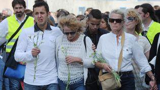 Des personnes participent à une marche silencieuse à Albi (Tarn), en hommage à l'enseignante mortellement poignardée dans sa salle de classe, le 7 juillet 2014. (ERIC CABANIS / AFP)