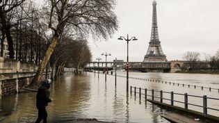 Un Parisien observe la crue de la Seine, près de la tour Eiffel, le 23 janvier 2018. (LUDOVIC MARIN / AFP)